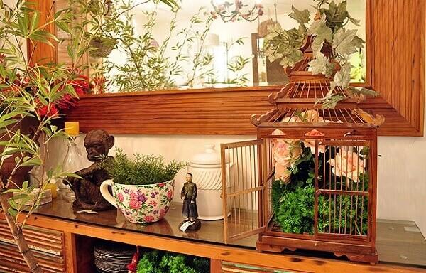 Gaiolas decorativas feitas em madeira servem de apoio para arranjos de flores