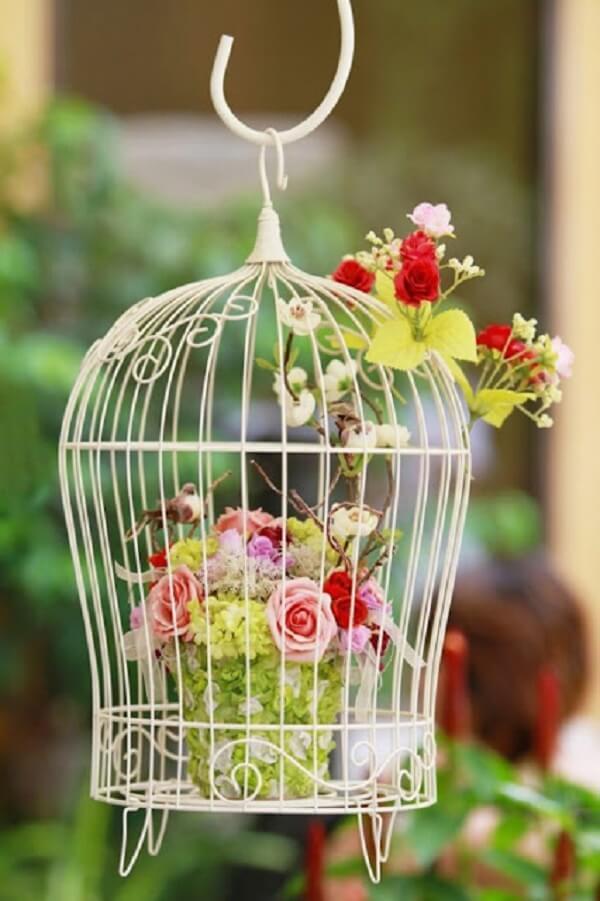 Gaiolas decorativas com arranjo de flores artificiais