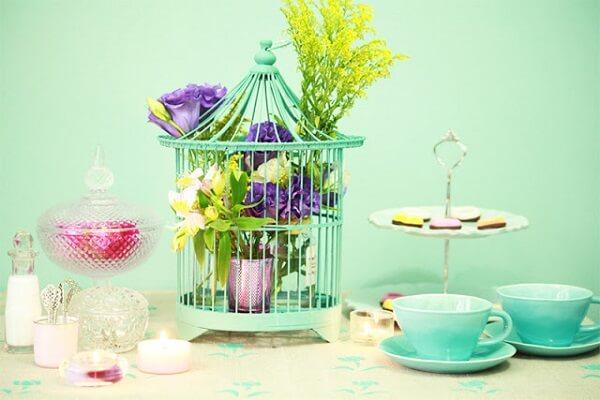 Gaiola decorativa com flores enfeita o centra de mesa da casa