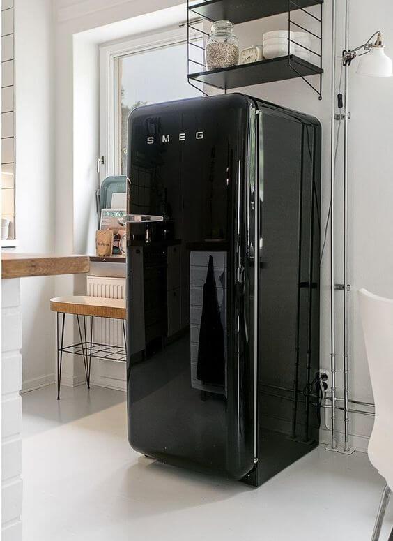 Geladeira preta na cozinha compacta
