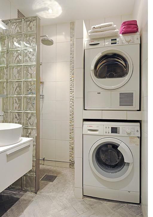 Lavadora de roupas branca em armário planejado