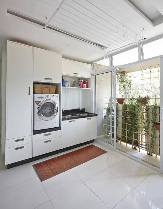 Lavanderia com armário planejado e lavadora de roupas frontal branca