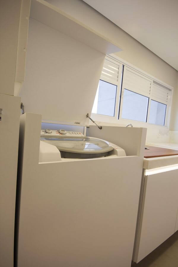 Lavadora de roupas escondida no armário da área de serviço