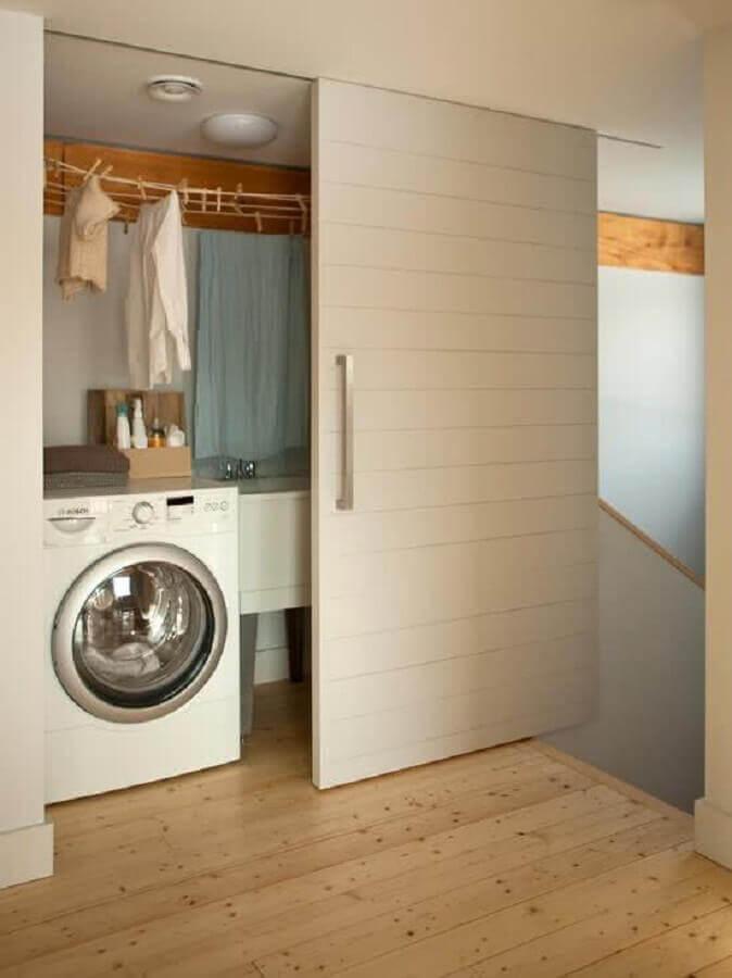 lavanderia pequena planejada com porta de correr e máquina de lavar e secar roupas Foto Prosa de Designer