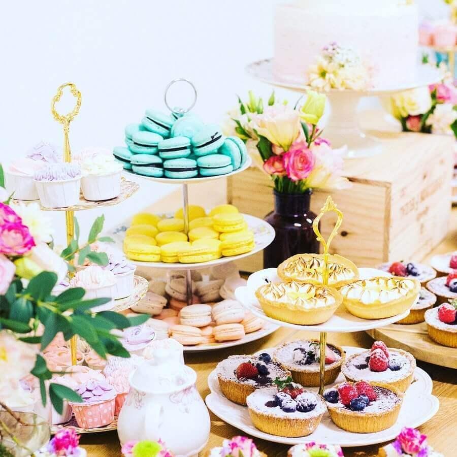 mesa de guloseimas decorada com arranjo de flores e macarons coloridos Foto White Spatula