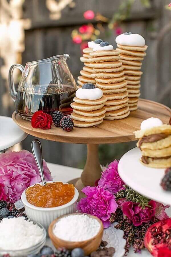mesa de guloseimas decorada com arranjo de flores e pratos de madeira Foto Ideias Decor
