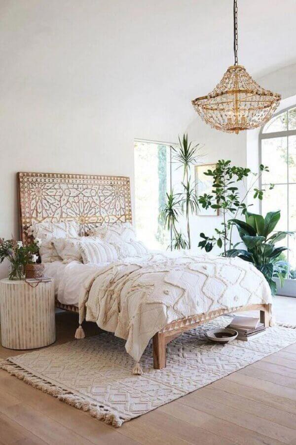 pendente para quarto de casal decorado com cama de madeira e vasos de plantas Foto Anthropologie