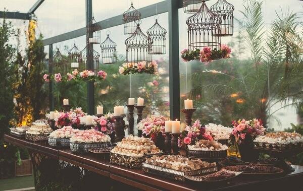 Decoração vintage para casamento com gaiolas suspensas em cima d mesa do bolo