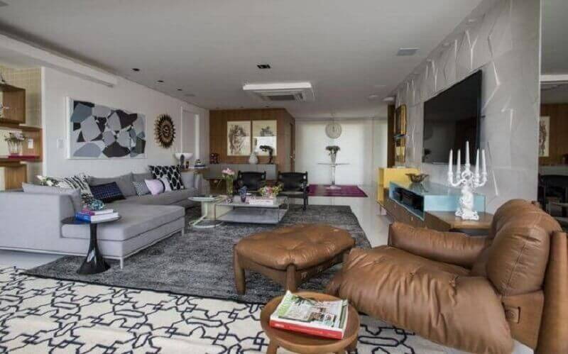 sala de estar ampla decorada com tapete cinza e poltrona de couro Foto Rodrigo Maia Arquitetura
