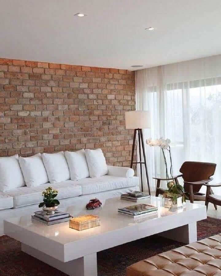 sala de estar decorada com parede de tijolinho e sofá branco de couro Foto Ideias Decor