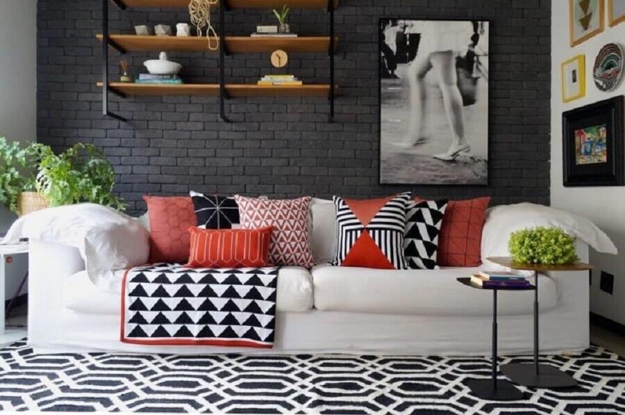 sala decorada com parede de tijolinho preto e sofá branco com almofadas coloridas Foto Mandril Arquitetura