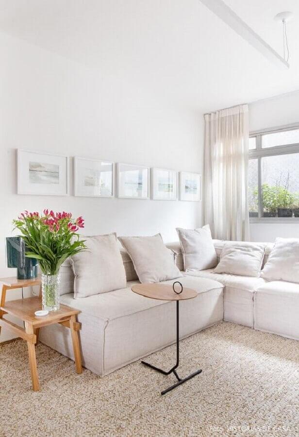 sala decorada com sofá branco de canto e mesa lateral de madeira Foto Histórias de Casa