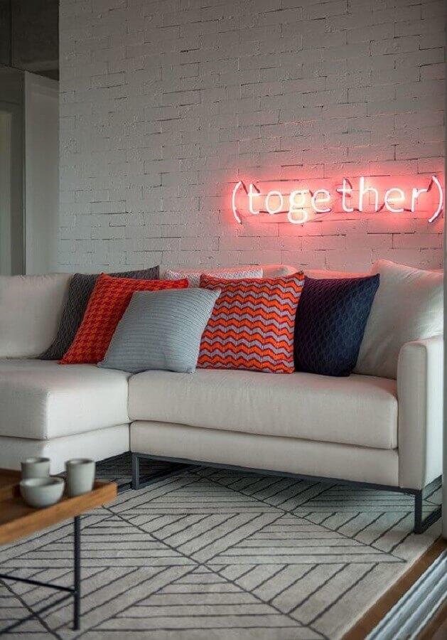 sala moderna decorada com luminária neon e sofá branco com almofadas coloridas Foto Casa de Valentina