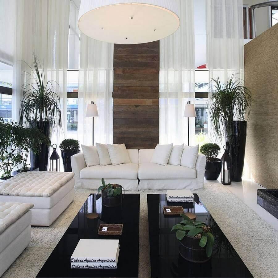 sala sofisticada decorada com sofá branco e mesas de centro pretas Foto Assetproject