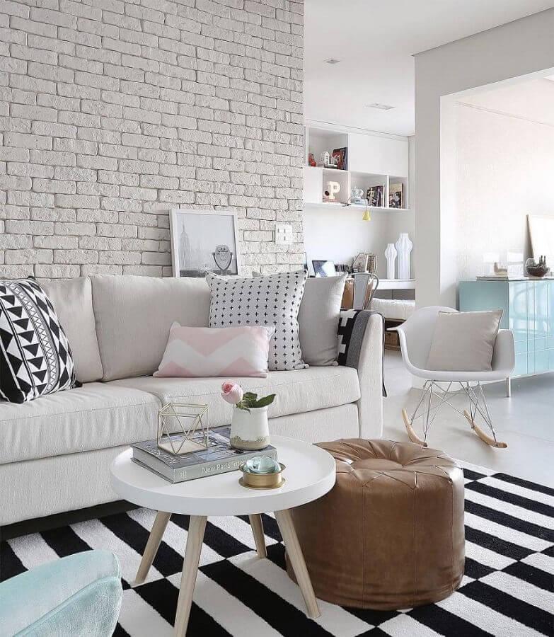 sofá branco de couro para sala decorada com parede de tijolinho e tapete listrado Foto Assetproject