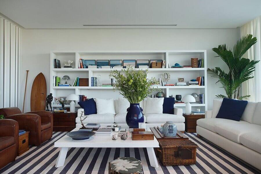 sofá branco para decoração de sala com tapete listrado e poltronas de couro Foto Radar Design