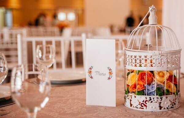 Gaiola decorativa enfeita o centro de mesa da festa de casamento