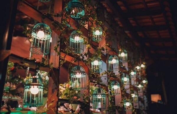 Parede formada em madeira e gaiolas decorativas separam os ambientes da festa