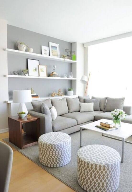 tapete cinza claro para decoração de sala clean com prateleiras brancas e puff redondo Foto We Heart It