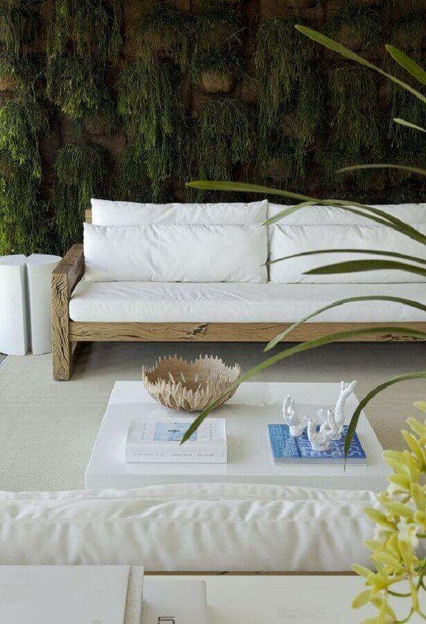 varanda decorada com jardim vertical e sofá branco com base de madeira Foto Diego Revolto Arquitetura