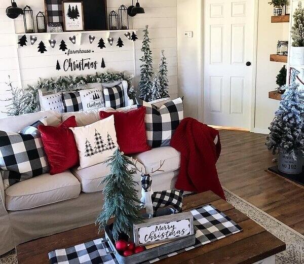 Sala de estar decorada com diversos elementos natalinos incluindo almofadas de Natal com diferentes estampas