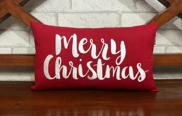 """Almofada de Natal em tom vermelho com escrita """"Merry Christmas""""."""