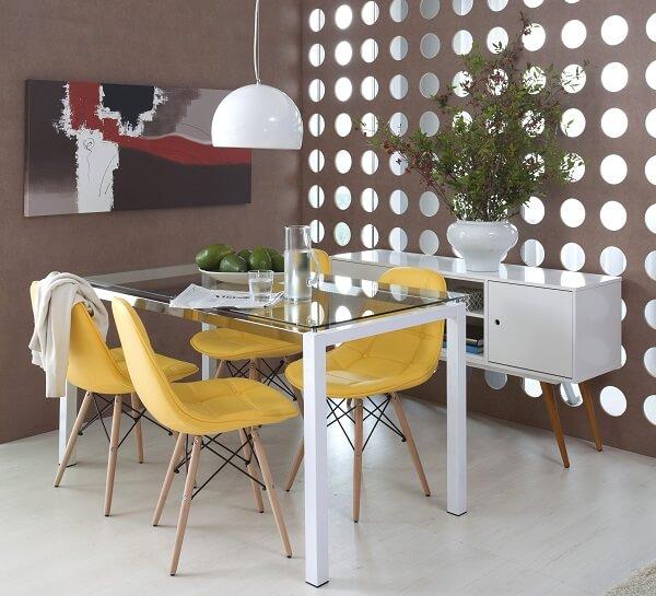 Sala de jantar com mesa de tampo de vidro e cadeira amarela estofada