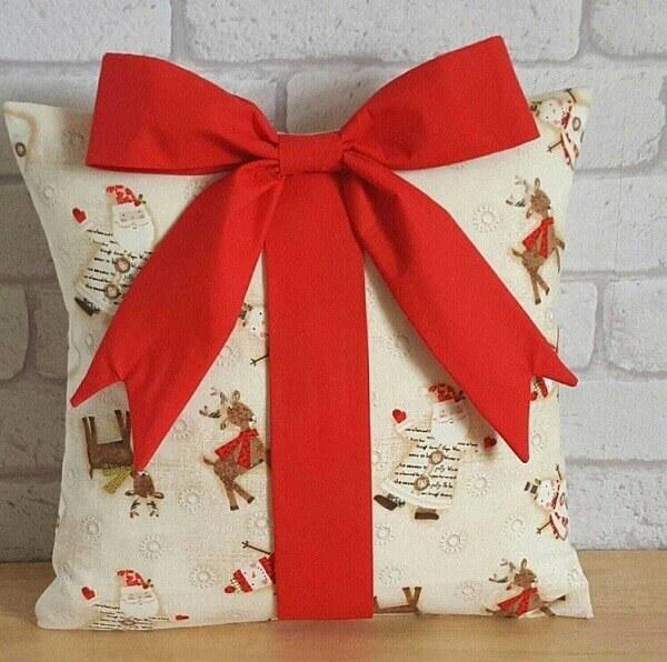Invista em almofadas de Natal com estampa fofa e laço de fita vermelho