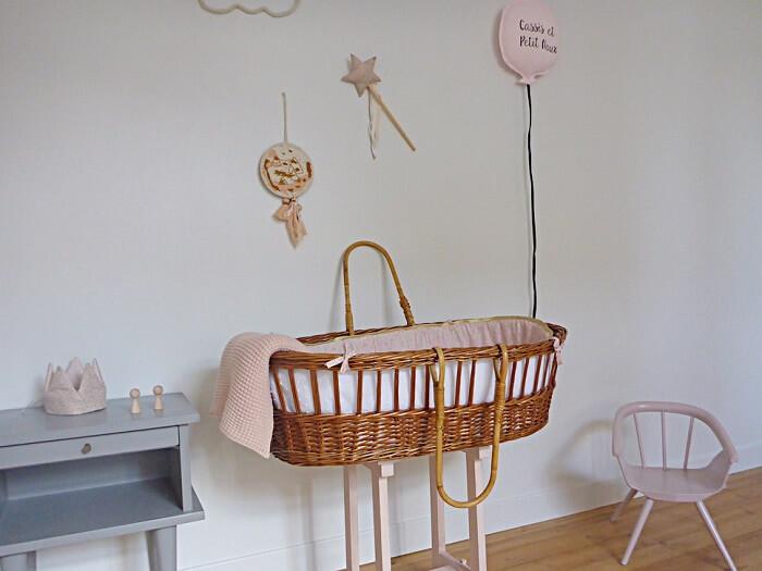 Quarto de bebê com berço cesto de vime e decoração delicada