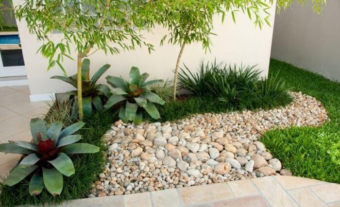 Jardim pequeno com bromélias, grama preta e pedras