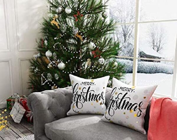 Sala de estar com árvore grande e almofadas de Natal