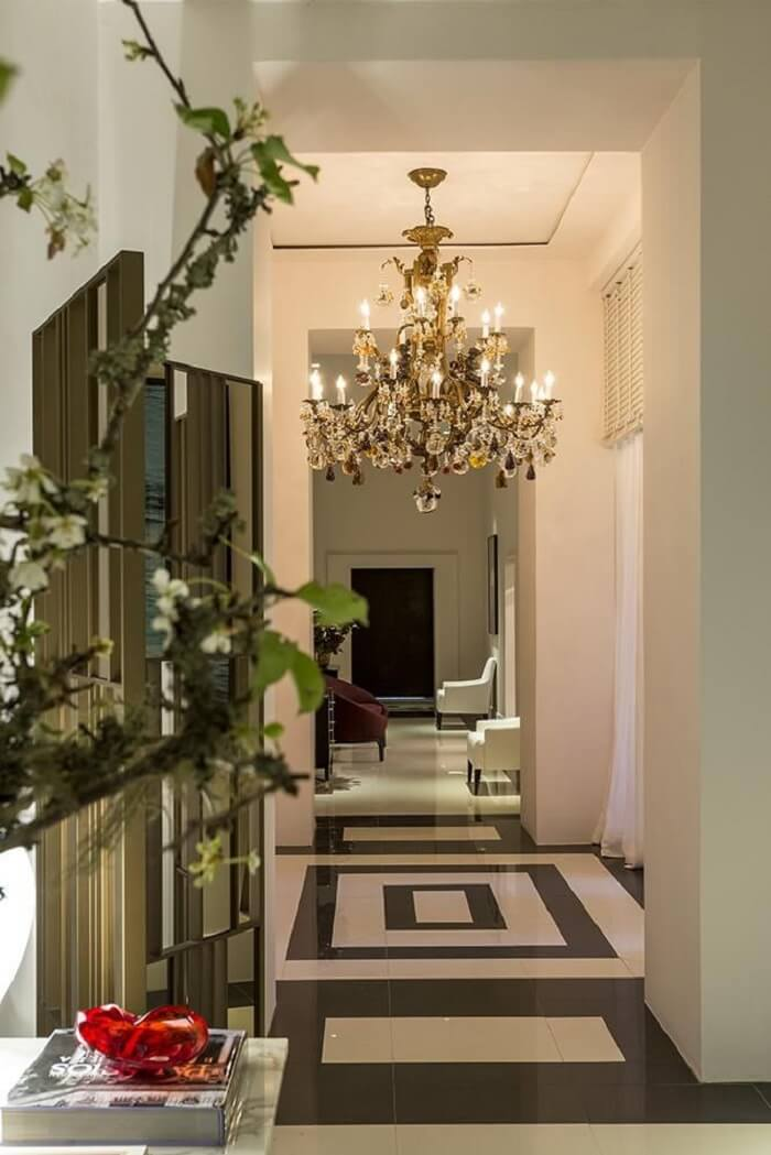 A decoração do corredor conta com a presença de um lustre