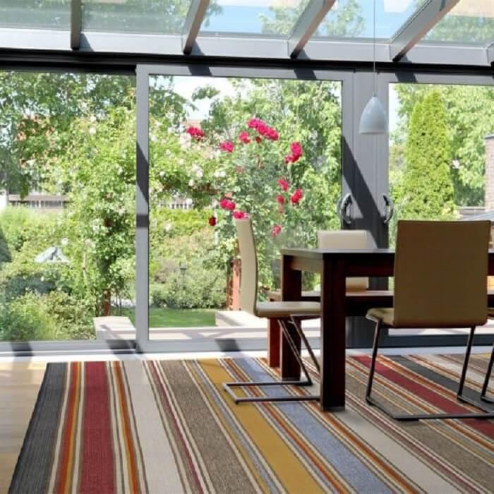 Ambiente com teto de vidro e tapete sisal colorido
