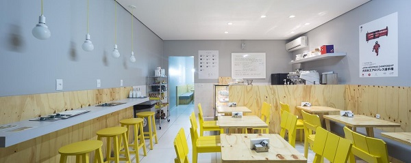Ambiente comercial com cadeira amarela e mesas de madeira