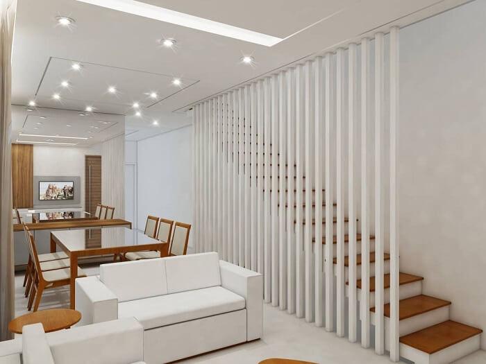 Sala com escada e guarda corpo feito de ripas brancas