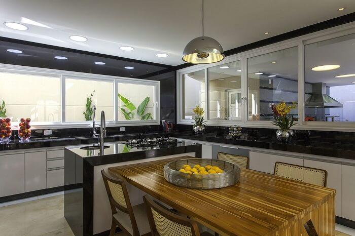 Bancada de granito preto, mesa de madeira comum e torneira gourmet