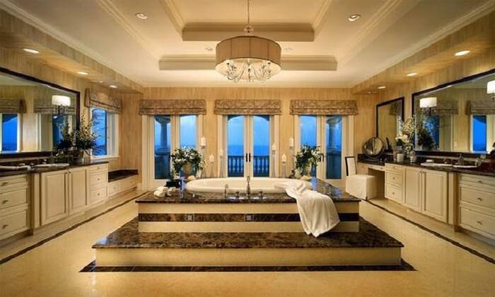 Banheiro amplo com lustre de cristais fixado no centro do cômodo
