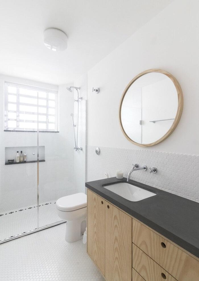 Banheiro clena conta com moldura para espelho amadeirada segundo o estilo das portas da bancada da pia