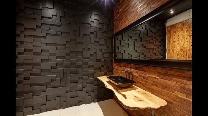 Banheiro sofisticado conta com placa de gesso 3D em tom preto