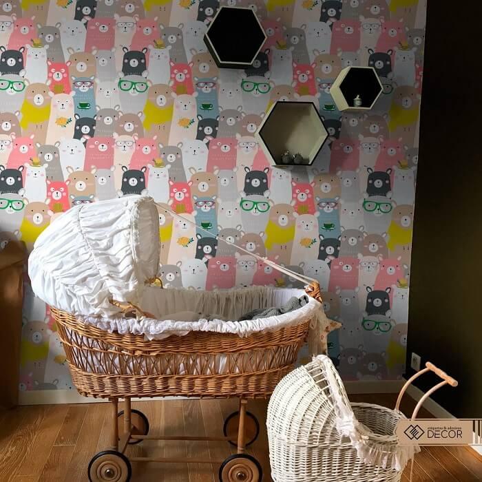Berço de vime e papel de parede ilustrado para quarto de bebê