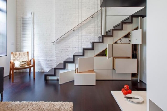 Sala com escada criativa que maximiza o espaço da casa