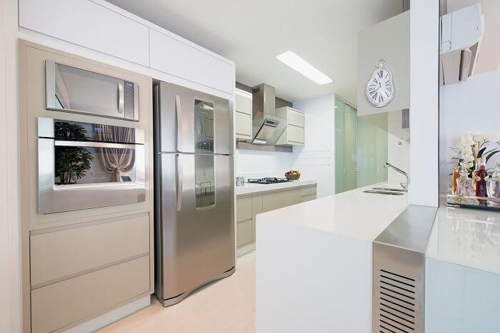 Cozinha com bancada branca e relógio de parede com design criativo