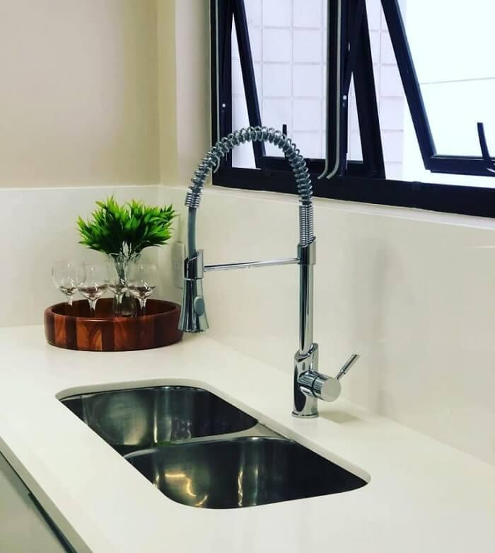 Cozinha com bancada branca e torneira gourmet de alumínio