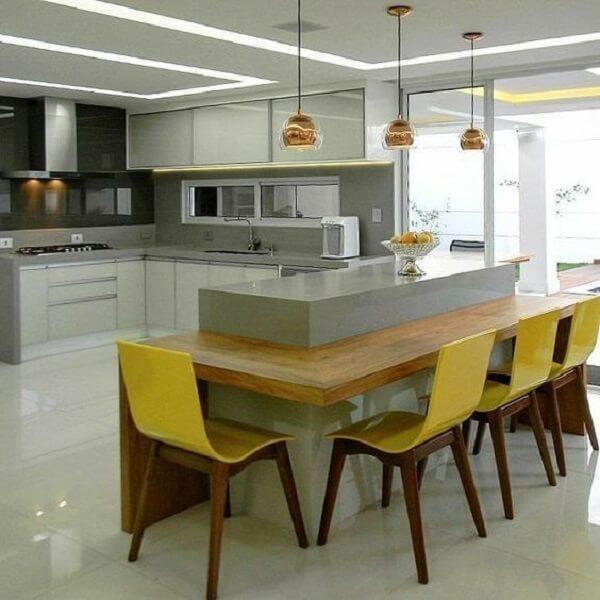 Cozinha com bancada de madeira embutida e cadeira amarela