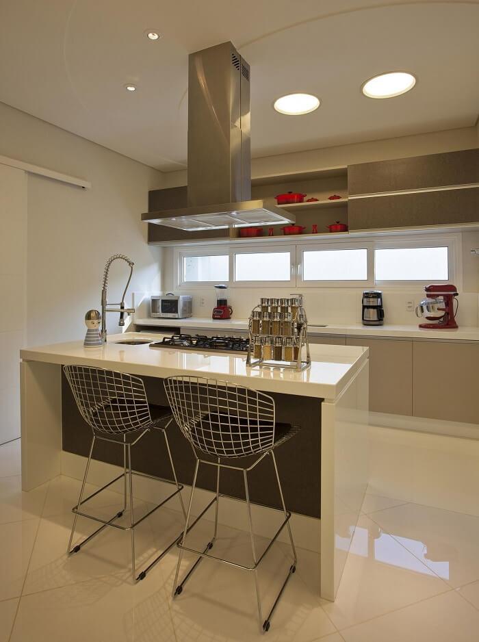 Cozinha com cadeira aramada e torneira gourmet