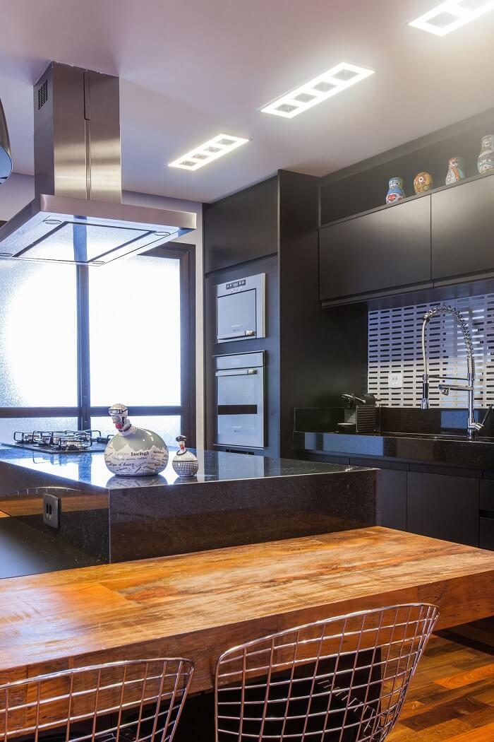 Cozinha com decoração escura e torneira gourmet
