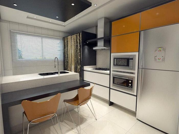 Cozinha compacta com cadeiras laranjas e torneira gourmet de mesa