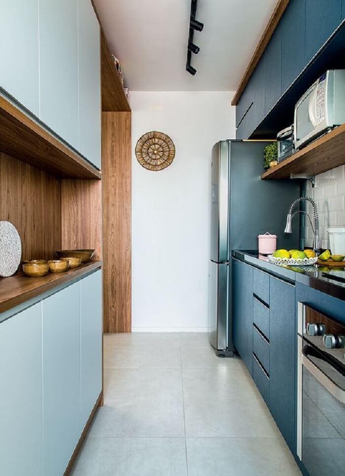 Cozinha compacta com marcenaria azul, iluminação preta e torneira gourmet