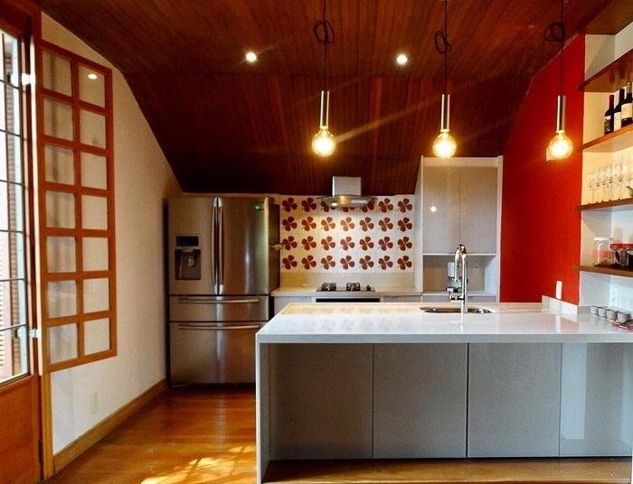 Cozinha em tons branco e vermelho conta com torneira gourmet de alumínio