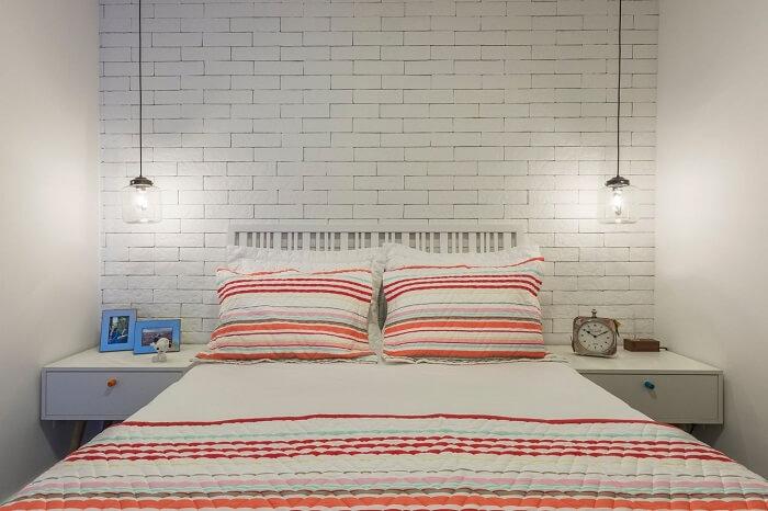 Criado mudo branco se harmoniza com a parede de tijolinhos do quarto